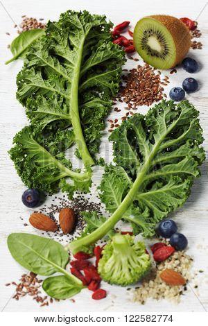 Healthy green smoothie or salad ingredients on white - superfoods, detox, diet, health or vegetarian food concept