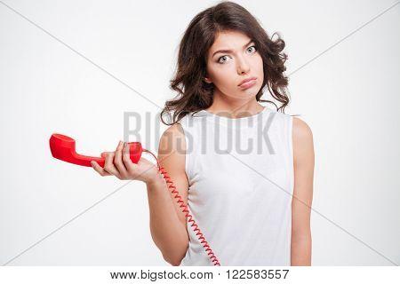 Sad woman holding phone tube isolated on a white background