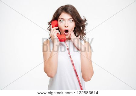 Amazed woman talking on the phone tube isolated on a white background