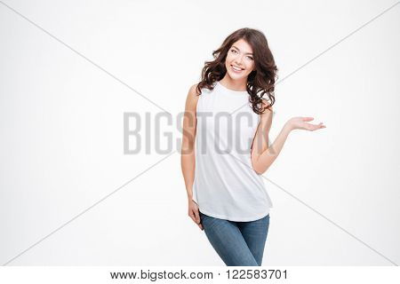 Smiling casual woman holding copyspace on the palm isolated on a white background