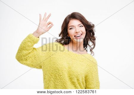 Portrait of a happy young woman showing ok sign with fingers isolated on a white background
