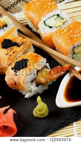 Arrangement of Maki Sushi with Smoked Salmon and Eel with Black Caviar on Stone Plate with Soy Sauce Ginger and Pair of Chopsticks closeup on Straw Mat background