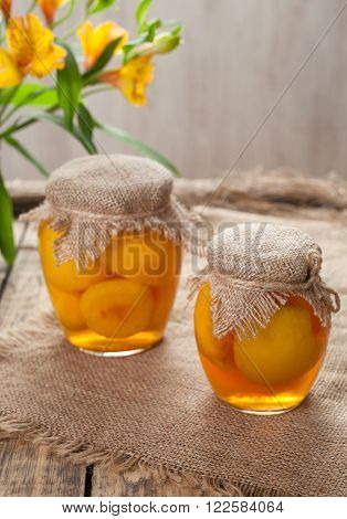 Canned peach compote in glass jars sweet traditional food on vintage cloth background