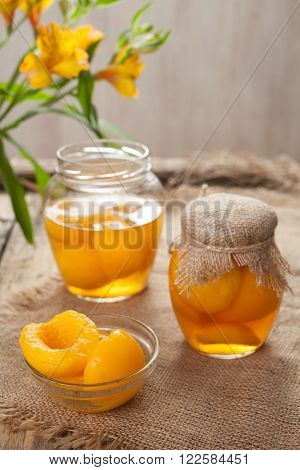 Traditional preserved peaches compote with juice in glass jars on vintage table