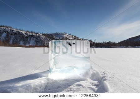 cube of ice on the snow against the backdrop of the hills