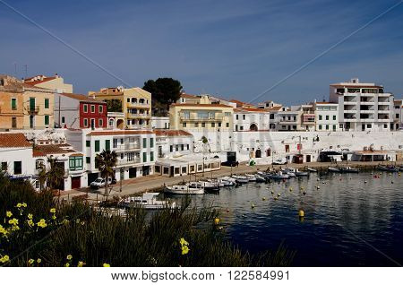 Es Castell Harbor Seafront and Lagoon on Blue Skies background Menorca Balearic Islands