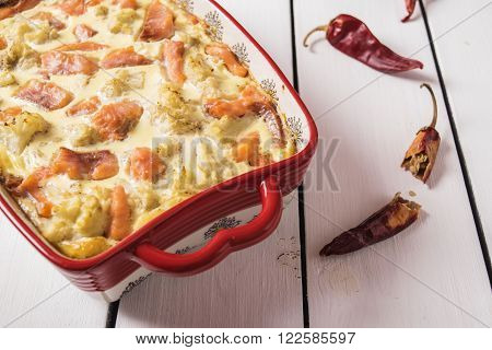 Casserole cauliflower and salted salmon with cream filling in a ceramic form on a white wooden background