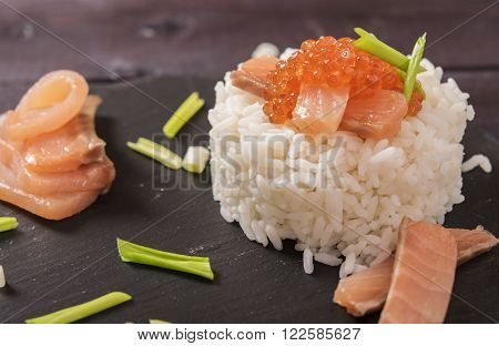 Appetizer of rice, salted salmon, red caviar and green onion on a shale plate