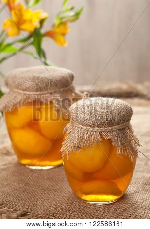 Glass jars with healthy canned peaches compote natural preserved fruits on vintage cloth background