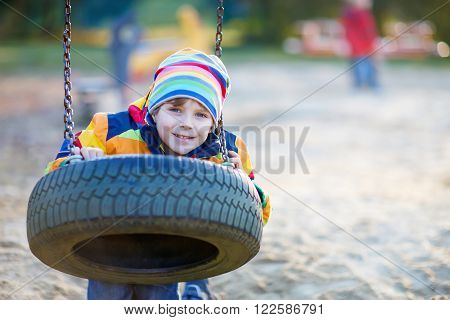 Adorable little kid boy having fun with chain swing on outdoor playground. child swinging on warm sunny spring or autumn day. Active leisure with kids. Boy wearing colorful clothes