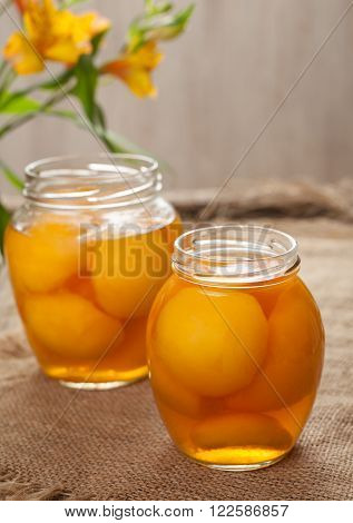 Canned natural peaches in glass jars with compote on vintage cloth background