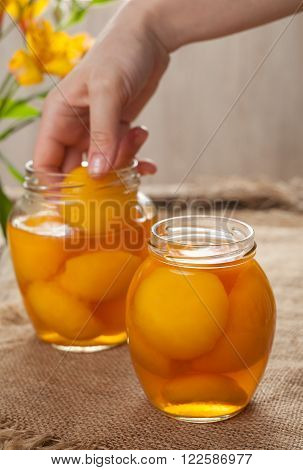 Canned natural vegetarian peaches in glass jars with compote on vintage cloth background