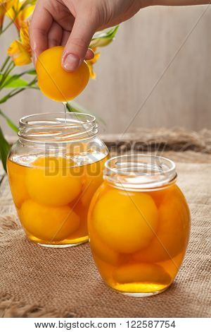 Traditional peach compot in glass jars, healthy preserved dessert on vintage wooden table