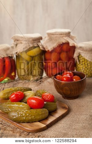 Pickled preserved homemade vegetables in glass transparent jars, cucumbers, pepper, tomatoes and peas on vintage table background