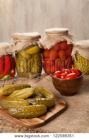 Pickled preserved vegetables in glass jars, cucumbers, pepper, tomatoes and peas on vintage table background
