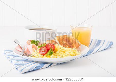 Breakfast of scrambled eggs ham and toast.