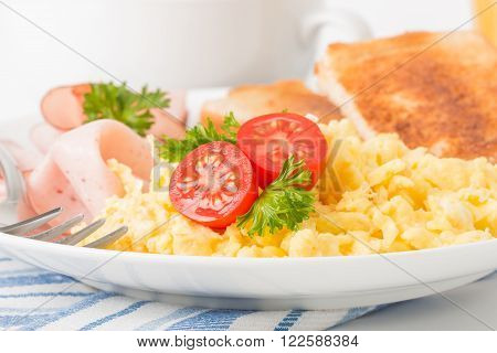 Scrambled eggs and ham with fresh tomatoes photographed closeup.