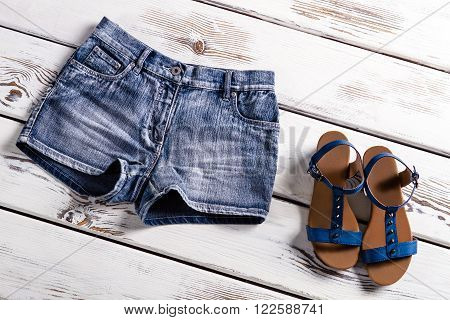 Lady's blue shorts and sandals. Woman's clothing on white shelf. Short jeans shorts with sandals. Girls' summer collection.