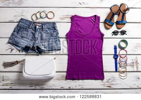Woman's purple top and shorts. Stylish clothes on old shelf. Lady's outfit with purple top. Warm season outfit for ladies.