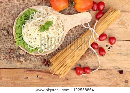 Spaghetti and raw spaghetti on wood background