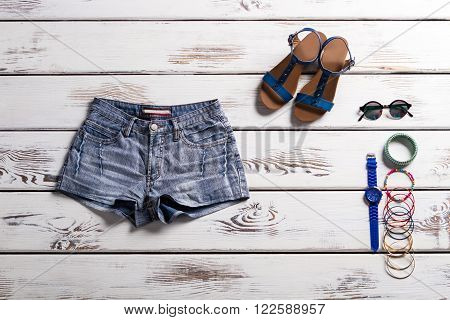 Classic denim shorts and footwear. Showcase with summer clothing. Vintage shorts and nice accessories. Sandals, shorts and small accessories.
