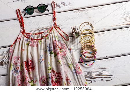 Vintage sarafan and round sunglasses. Stylish clothing on wooden background. Trendy garment for young women. Light clothes on workshop table.