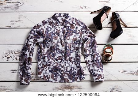 Woman's floral shirt and shoes. Trendy clothes on wooden background. Shirt of popular design. Frosted heel shoes and shirt.