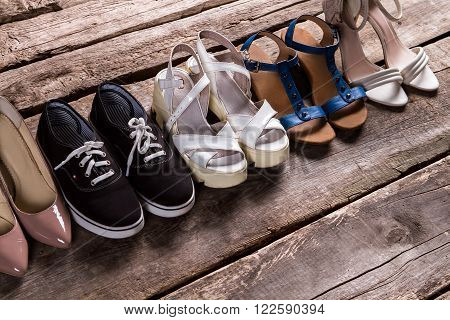 Female shoes on old floor. Tankette shoes and fabric keds. Footwear for every taste. From simplicity to luxury.
