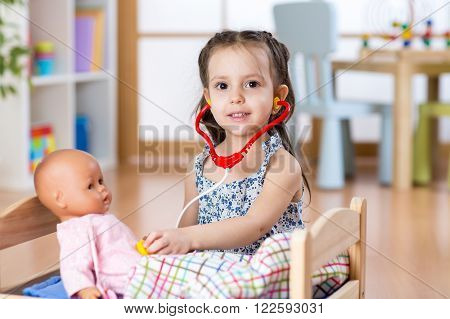 Kid girl playing doctor role game examining her doll using stethoscope. Child sitting in playroom at home, preschool or kindergarten