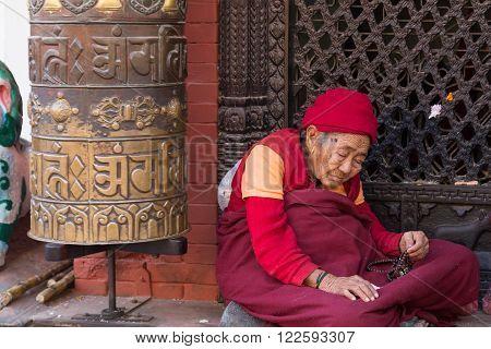 Kathmandu, Nepal - December 03, 2014: Pilgrim visiting the Buddhist Boudhanath Stupa.