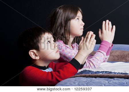Siblings say bedtime prayers.