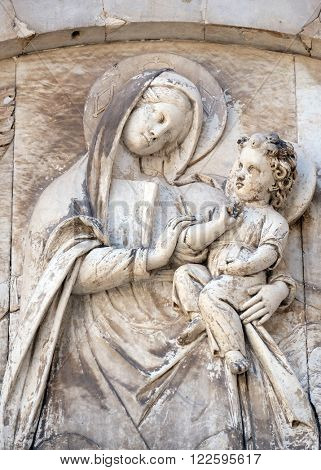 LUCCA, ITALY - JUNE 06, 2015: Bas-relief representing the Virgin Mary with baby Jesus, Cathedral of S.Martino in Lucca, Italy, on June 06, 2015
