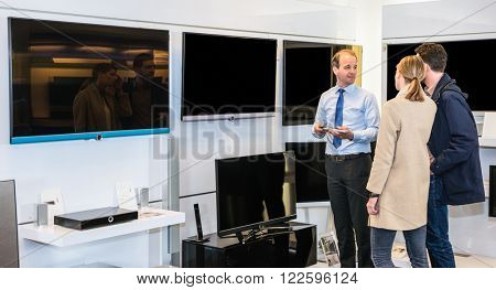 Mature assistant showing flat screen TV to young couple in electronics section of hypermarket