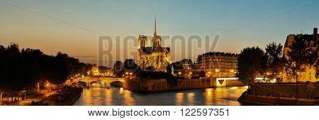 Notre Dame de Paris at dusk panorama over River Seine as the famous city landmark.