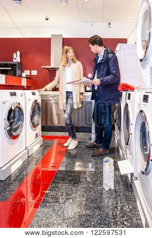 Full length of young couple choosing washing machine in hypermarket