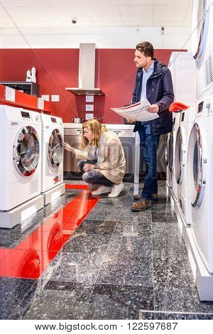 Young man holding pamphlet while woman examining washing machine in hypermarket