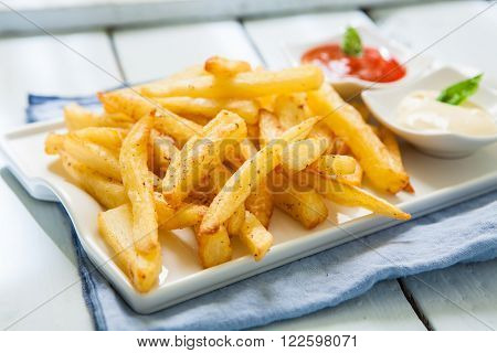 deep fried french potato with sauces on tray