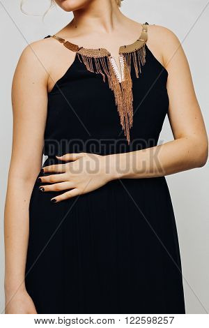 elegant fashionable black dress with gold jewelry on a beautiful young blonde girl fashion model with curly long blond hair chic luxury manicure on nails, isolated on white background