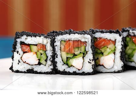 Japan square black tobiko rolls with shrimp, salmon and cucumber copyspace