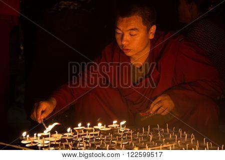 Kathmandu, Nepal - December 06, 2014: Buddhist pilgrim at Boudhanath stupa lighting up butter candles for full moon festival.