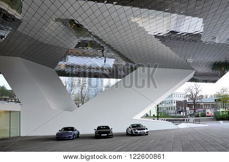 STUTTGART GERMANY - APRIL 13 2015: Porsche Museum cars. The entrance area with a mirrored canopy and three parked cars. Stuttgart Baden-Wurttemberg Germany.