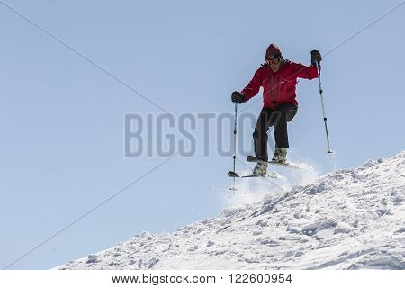 Sofia Bulgaria - March 12 2016: A free rider is jumping from the edge of a while skiing down a snowy rocky mountain top. Clear blue sky.