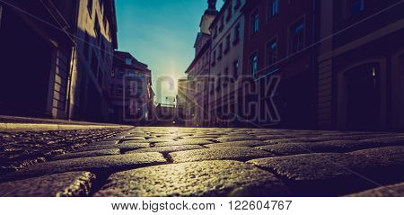 sunrise in the city on the street with paving stones