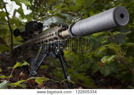 Silencer on the end of a semi automatic rifles in the bushes
