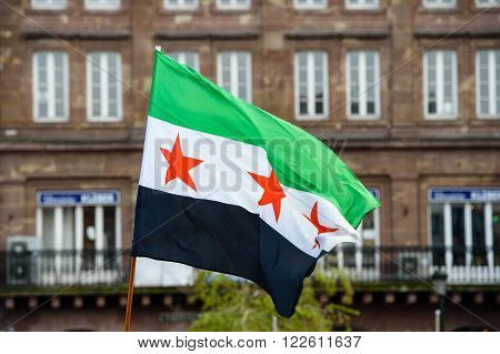 STRASBOURG FRANCE - MAR 19 2016: National flag of Syria waving during protest with European architecture in the background