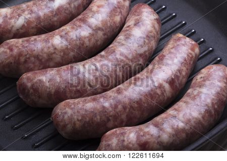 raw beef sausage in a frying pan, rustic