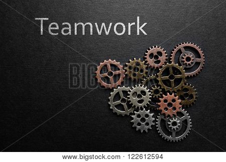 Small metal gears with Teamwork text on dark background