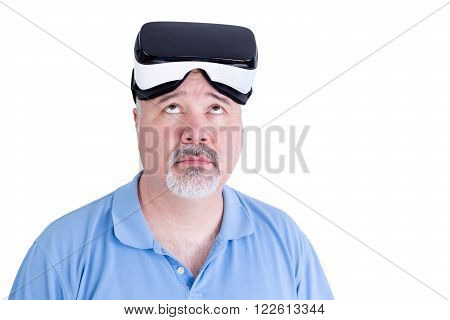 Adult male with virtual reality glasses on his head wearing blue polo shirt against a white background looks up questioning