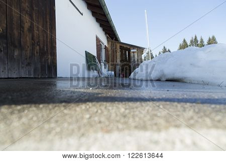 A low angle photo on a concrete plat form in front of the storage area and some melting snow