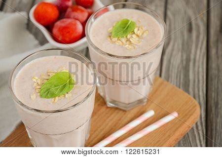 Strawberry and banana smoothie with oatmeal on the rustic wooden table. Horizontal permission. Selective focus. Copy space.